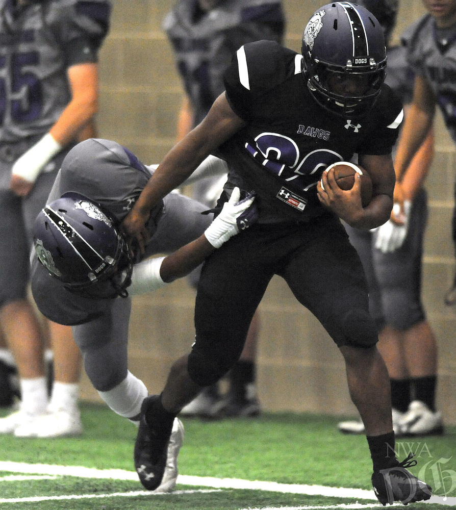 NWA Democrat-Gazette/ANDY SHUPE<br /> Javontae Smith (right) of Fayetteville carries the ball Friday, May 29, 2015, as Cemari Dobbins attempts to make the tackle during the Bulldogs' annual Spring Game inside the school's indoor facility in Fayetteville. Visit nwadg.com/photos to see more photographs from the game.