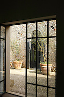 The mellow stone walls of the inner courtyard of the manor house glimpsed through an open door