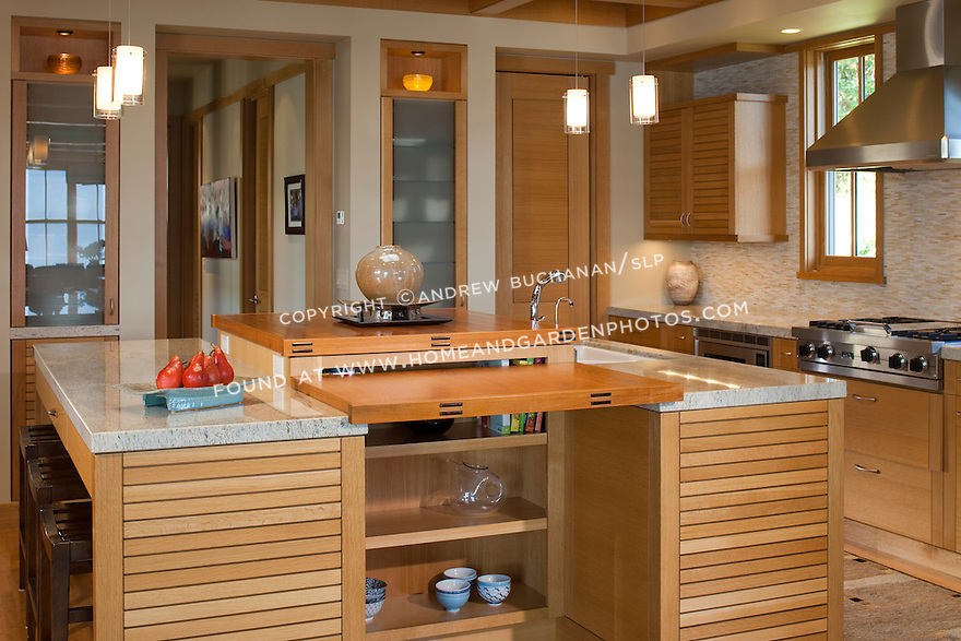 A unique, three-part kitchen island is the heart of this open, airy kitchen. This image is available through an alternate architectural stock image agency, Collinstock located here: http://www.collinstock.com