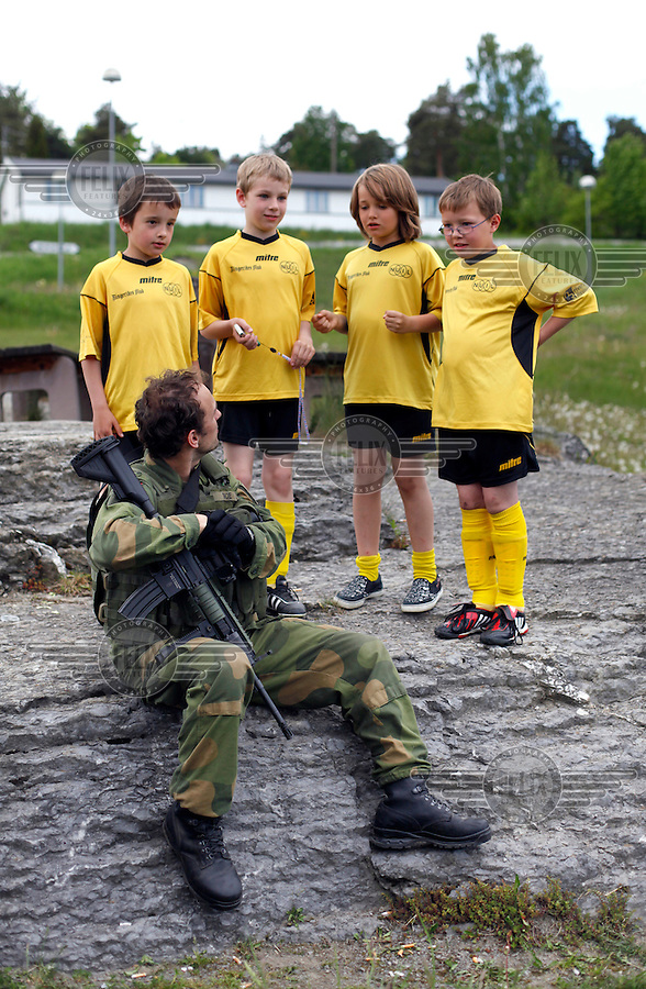 Children from Norderhov football team surrounds Kim Moe during a break. Norwegian Home Guard soldiers during exercise Djerv..The Home Guard has traditionally been designated to secure important  domestic installations in case of war or crisis. With the cold war long gone, a war in Afghanistan and budget cuts, there is a debate over the Home Guard's role in the future.