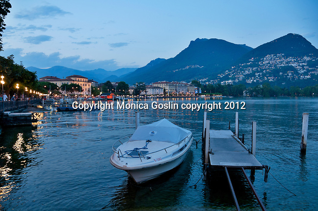A boat on Lake Lugano, Switzerland at night, with the city of Lugano in the background