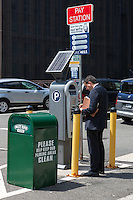 A man pays for parking at a solar powered multi-space pay station at a municipal parking lot in White Plains, New York.
