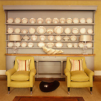 A large antique dresser painted grey in pleasing contrast to two armchairs upholstered in imperial yellow in the lounge of The Soho Hotel in London