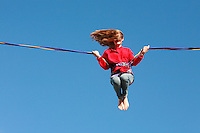 Brighton, England - child having fun on a giant elastic cord &quot;ride&quot; on Brighton beach - Photograph by Owen Franken