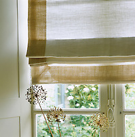 A linen Roman blind edged in textured fabric