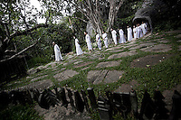 "MAE CHEE KON KHAI leads a walking meditation to a female group as part of the Sathira Dhammasathan spiritual teaching program for the lay people. Vanished by centuries the lineage of ""Bhikkhu?nii"" (Order of Nuns) has been brought to the ongoing Thai society's debate. White-clad thai nuns, who keep the eight precepts and have their heads and eyebrows shaved are known as the lon-existing ""mae chees"" (low category to call the lay nuns). Females who have turned to religous life, as renunciants, live ostracized and marginalized by the Sangha (Buddhist community) and Thai society, denying them full access to the monastic life as well as rights and support from the government. Today nunhood is not recognized by any asian country belong to the Theravada Buddhist order. Most of the eight precept holders live in temples run by male abbots, at the shadow of the monks; with the exceptional existence of a few para-monastic institutions as the Sathira Dhammasathan meditation centre, where ""mae chees"" are not allow to held a temple, but not denied to practice the spiritual life."