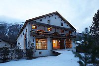 The windows of the chalet lit up at dusk