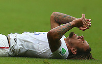 Jermaine Jones of USA feels the pain after being hit in the face with the ball