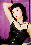 A woman in a black vintage corset, siting on the bed , with hand in her dark hair