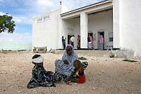 A woman sits with her two children outside the Daawad hospital in Eyl, after one of her children was treated by doctors.