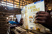 A child holds a French language text book in the village school. Doctor Richard Hardi and his medical medical team have come to the remote village of Pania to perform eye surgery. <br /> <br /> From his base in Mbuji Mayi Hungarian ophthalmologist Friar Richard Hardi and his team travelled deep into the Congolese rainforest, by 4x4 and canoe, to treat people in isolated communities most of whom have never seen an ophthalmologist. At a small village called Pania they established a temporary field hospital and over the next three days made hundreds of consultations. Although both conditions are preventable, many of the patients they saw had Glaucoma or River Blindness (onchocerciasis) that had permanently damaged their eyesight. However, patients with cataracts, a clouding of the eye's lens, who were suitable for treatment were booked for an operation. For two days the team carried out the ten minute procedure on one patient after another. The surgery involves making a 2.2mm incision into the remove the damaged lens that is then replaced by an artificial one. Doctor Hardi is one of the few people willing to make such a journey but is inspired to do so by his faith and, as he says: 'Here I feel that I can really make a difference in people's lives'. /Felix Features