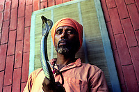 On the outskirts of Delhi a charmer shows his skills in handling a Cobra..