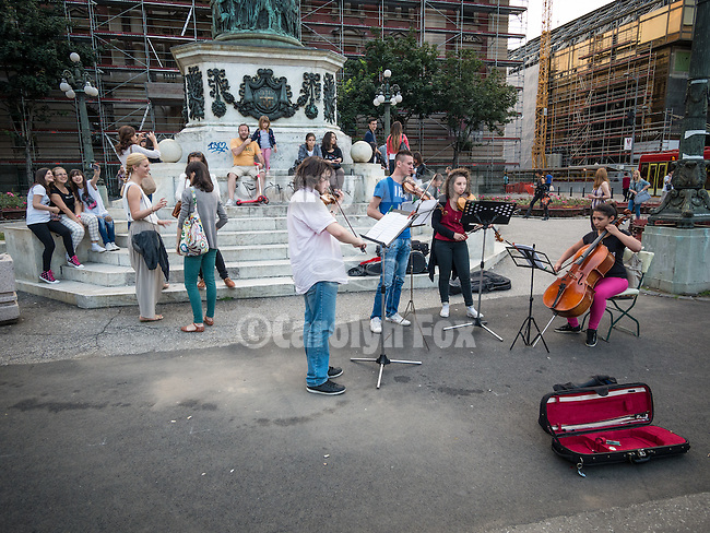 Street musicians gather and play for tips at the base of the Prince Mihalo Monument, Republic Square, Belgrade, Serbia