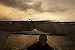 Scot Janikula watches the clouds start to change color during sunset as he navigates his skiff back to his houseboat, anchored in Estero Bay.