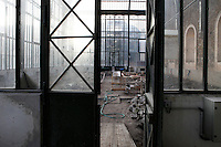 New Caledonia Glasshouse (formerly The Mexican Hothouse), 1830s, Charles Rohault de Fleury, Jardin des Plantes, Museum National d'Histoire Naturelle, Paris, France. Low angle view of renovation works on the glass and iron structure, seen through the door from a passageway. In the distance, through the glass wall, may be seen the Plant History Glasshouse (formerly Australian Glasshouse), 1830s, Rohault de Fleury. The New Caledonia Glasshouse, or Hothouse, was the first French glass and iron building.