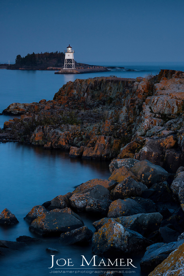 Dusk over breakwater and Grand Marais lighthouse on Lake Superior.