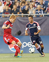 New England Revolution midfielder Diego Fagundez (14) dribbles down the wing as Chicago Fire midfielder Jeff Larentowicz (20) closes. In a Major League Soccer (MLS) match, the New England Revolution (blue) defeated Chicago Fire (red), 2-0, at Gillette Stadium on August 17, 2013.