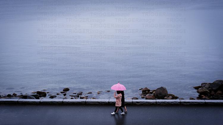 Two women walking under pink striped umbrella against dark ocean on rainy day.