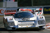 The Porsche 962 of Bob Wollek and Paolo Barilla lifts a wheel during hard cornering in the 1986 IMSA GTP race in Miami, Florida.