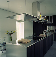 A stainless steel kitchen island provides ample room for a sink, hob and generous amounts of worktop and cupboard space