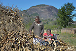 Peter Makura shucks corn at his home in the village of Berejena, near Masvingo, Zimbabwe, with help from Sonica Sadzauchi, a community rehabilitation worker for the Jairos Jiri Association, which provided Makura with his wheelchair with support from CBM-US.