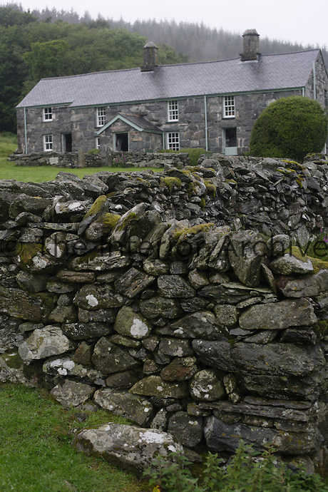 Front facade of Garth Gell seen from over a dry stone wall