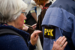 A elderly woman puts a sticker on her partner's jacket in protest of Nuclear Energy at a Rally against Nuclear Energy held on the Dam Square in Amterdam, the Netherlands on April 16, 2011.Thousands of people gathered on the square to protest recent Netherlands government movements to increase nuclear power in the country.