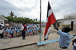 Children observe as the national flag is lowered at the end of the day at a school in Batey Bombita, a community in the southwest of the Dominican Republic whose population is composed of Haitian immigrants and their descendents.
