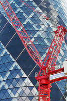 Red HTC crane in front of the Gherkin (St Mary's Axe).<br />