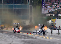 Mar 14, 2015; Gainesville, FL, USA; NHRA top fuel dragster driver Larry Dixon (right) races alongside Doug Kalitta as he crashes after his car broke in half during qualifying for the Gatornationals at Auto Plus Raceway at Gainesville. Dixon walked away from the incident. Mandatory Credit: Mark J. Rebilas-