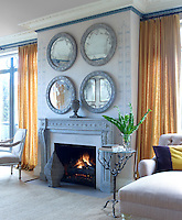 The stone fireplace in the living room is Louis XVI, flanked on either side by floor to ceiling linen curtains