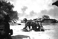 It appears that one Marine is relieving another on the beach at Saipan but they are really crawling under enemy fire, to their assigned positions.  June 1944.  Sgt. James Burns.  (Marine Corps)<br /> Exact Date Shot Unknown<br /> NARA FILE #:  127-GR-113-83260<br /> WAR &amp; CONFLICT BOOK #:  1174