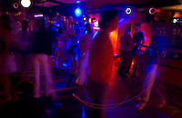 With a crowd only starting to arrive at 3:00 A.M., patrons blow smoke into the blue lights of the dance floor at the La Plage disco in Punta del Este, Uruguay. The venerable South American beach resort is having a rennaisance. (Kevin Moloney for the New York Times)