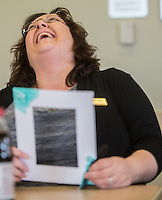NWA Democrat-Gazette/ANTHONY REYES @NWATONYR<br /> Melanie Hendrickson, circulation specialist with the Bentonville Public Library, laughs as she realizes her photo mat is glued to the table Friday, Feb. 10, 2017 while making the decorated mat at the library. The mat has a Valentine's Day theme made with lace, tulle and could fit a 5x7 photo.