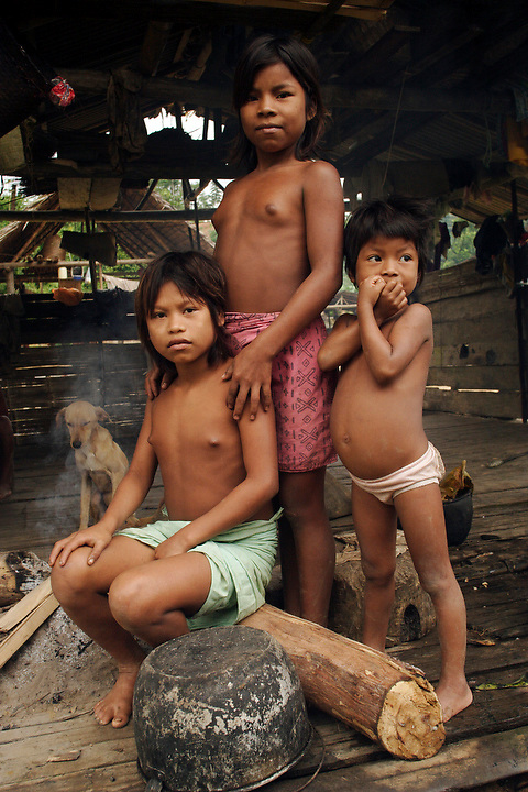 NUQUÍ, EL CHOCO, COLOMBIA -- DECEMBER 15:  A group of indigenous Colombian children pose in their simple house in a village near the town of Nuqui on December 15, 2005. Nuquí is a small town on Colombia's isolated and untamed Pacific coast, an area sandwiched between endless miles of trackless rainforest and the Pacific Ocean. (Photo by Dennis Drenner/Aurora).
