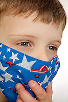 Little Boy with fun medical mask with ball desing in blue, pinc ,yellow, and purple