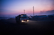 Trucks carry a load of coal out of the open cast mines in the early hours of the day in Bokapahari village in Jharia, outside of Dhanbad in Jharkhand, India.  Photo: Sanjit Das/Panos