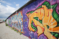The &quot;East Side Gallery&quot; is a preserved section of the Berlin Wall in the Friedrichshain District of former East Berlin. In the background is the Fernsehturm (televison tower and revolving restaurant) which became the iconic symbol of East Germany and Communist era technology when it was completed in 1969..