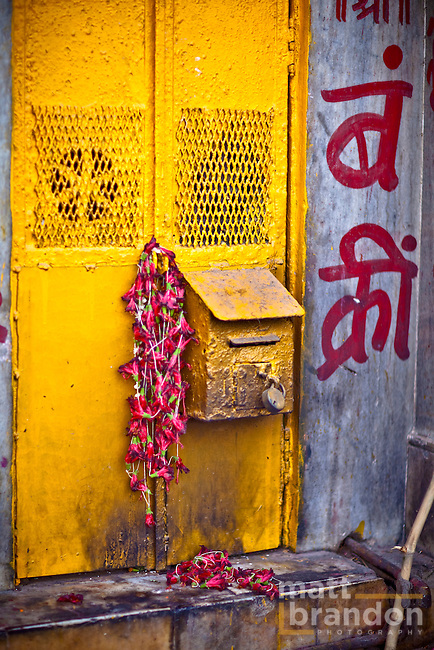 Here a yellow mailbox is draped with red flowers were left over from some puja.
