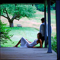 Couple lounging on edge of porch