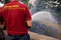 Roma 28 Giugno 2013<br /> Incendio di sterpaglie in via Casilina al civico 900, ex campo rom. Vigile del Fuoco durante le operazioni di spegnimento dell'incendio.