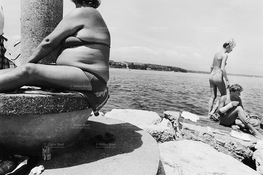 Switzerland. Geneva. Summer on the lake Geneva. A fat woman, seats on a concrete platform close to a column. A young couple enjoys sunbathing. The pretty young woman is up on her feet, she wears a string and is topless. The man is seated on the rock, he smokes a cigarette and has one's fore arm in plaster. © 1987 Didier Ruef