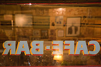 """Sports memorabilia and homages to tango singer Carlos Gardel reflect in the windows at Cafe de Garcia in Buenos Aires'  Villa Devoto neighborhood. Garcia, opened in 1937 by the Garcia family, wears its past on its """"sleeves."""" A Boca Junior T-shirt signed by Diego Maradona joins accordions, cue sticks, wine skins, rifles, and numerous vintage items on shelves and yellowed walls. (Kevin Moloney for the New York Times)"""