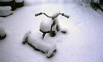 A childs trike covered in snow