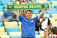 A Brazil fan holds a scarf up