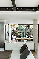 The living area is entirely open-plan with the dining area separated by a white Capellini lacquered sideboard