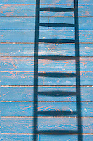 The shadow of a ladder on distressed blue floorboards