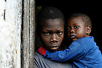 Nigenson Dupres, 15, holds his younger brother Jefte in the doorway to their home in Despagne, a rural village in southern Haiti where the Lutheran World Federation has been working with residents to improve their quality of life.