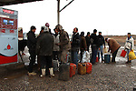 SHILAKAY, IRAQ: Syrian smugglers fill up their jerry cans at an Iraqi gas station...Due to the recent conflict in Syria there is a gasoline shortage in the country. Syrian smugglers purchase gasoline in Iraq and smuggle it into Syria for a profit of about $0.40 per liter. Smugglers carry between 10 and 30 liters per person on the 7 hour roundtrip journey that often takes them through frozen mud and snow...Photo by Aram Karim/Metrography