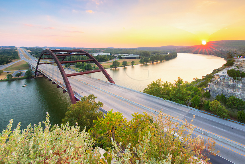 With day fading, the sun sets in the west over the Texas Hill Country. In the foreground is the iconic 360 Bridge, formally known as Pennybacker Bridge, just outside of Austin, Texas.